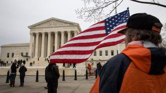 WASHINGTON, DC - FEBRUARY 19: Thomas Koors, of San Rafael, California, holds an American flag outside of the U.S. Supreme Court, February 19, 2016 in Washington, DC. After lying in repose at the Supreme Court on Friday, Justice Antonin Scalia's funeral is scheduled for Saturday at the Basilica of the National Shrine of the Immaculate Conception in Washington. (Photo by Drew Angerer/Getty Images)