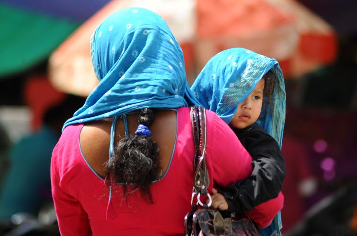 A woman covers herself and her child with a scarf as temperaturessoared to record highs.