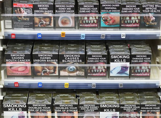 Cigarettes are being sold in standardised green packaging bearing graphic warnings of the dangers of...