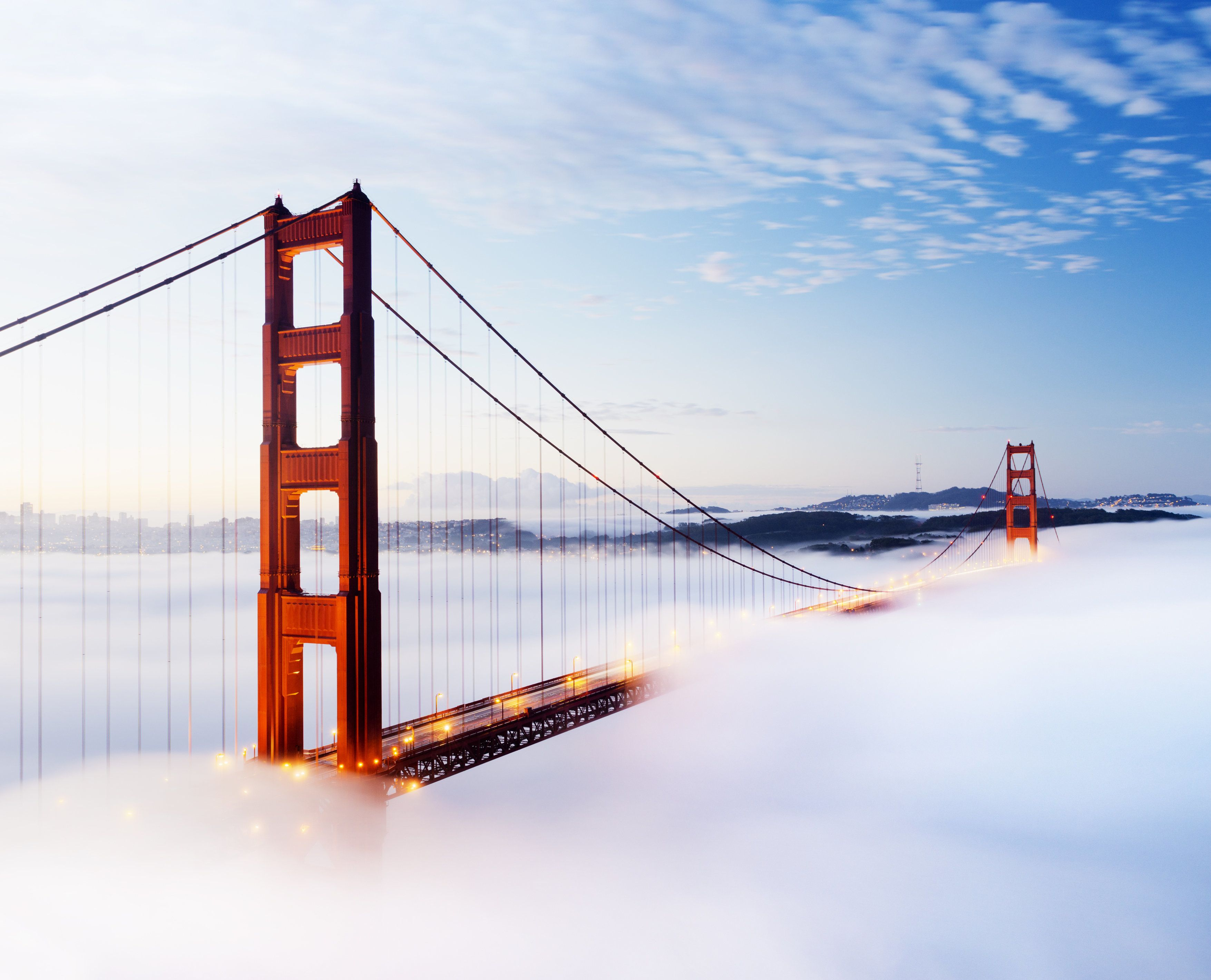 'The Golden Gate bridge in San Francisco surrounded by fog at twilight, USA.'