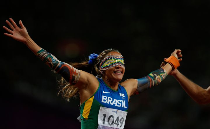 Brazil's Terezinha Guilhermina is held by her guide as she celebrates winning the women's 100m - T11 final in the Olympic Sta