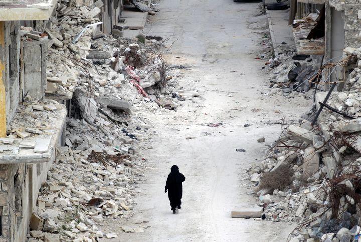 A woman walks past damaged buildings in Maaret al-Numan, a town in Syria's Idlib province. Women arestill marginalized,