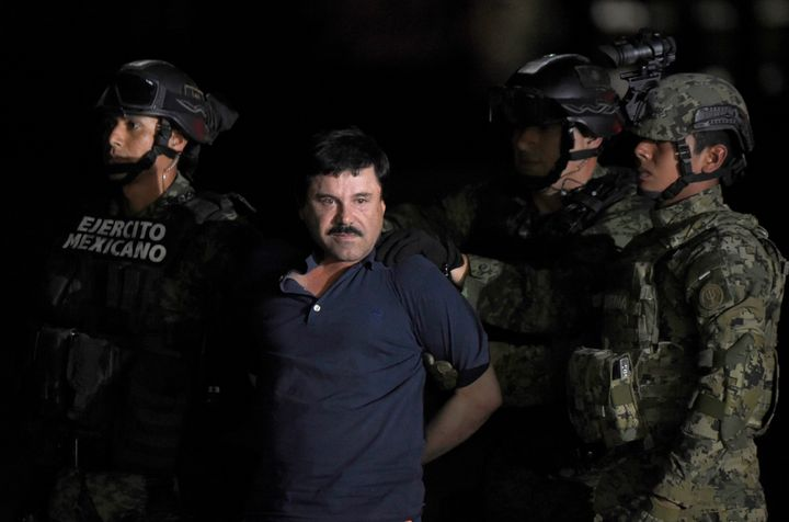 Drug kingpin Joaquin 'El Chapo' Guzman is escorted to a helicopter at Mexico City's airport following his recapture in Januar