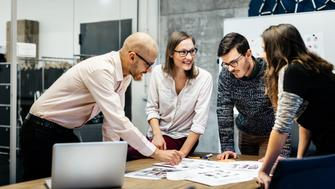 A team of four business people is standing in front a desk in a bright office room. They ambitiously point at documents while smiling and looking at the charts and notes.
