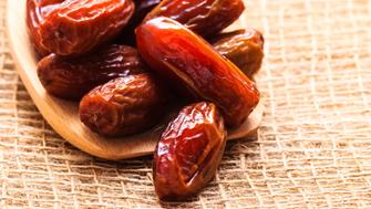 Healthy eating. Closeup dried dates on wooden spoon table sackcloth rustic background