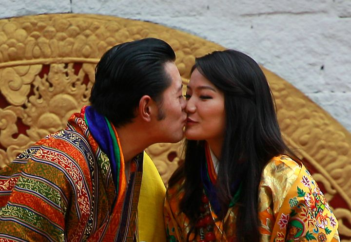 Bhutan's King Jigme Khesar Namgyal Wangchuck, left, and Queen Jetsun Pema kiss in front of the crowd at the main stadium as p