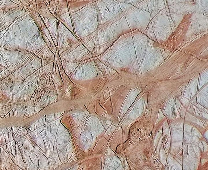 This is an enhanced-color view from NASA's Galileo spacecraft showing an intricate pattern of linear fractures on the icy sur