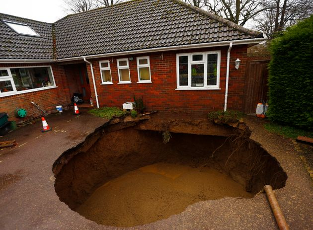 A 4.5 metre (15 feet) wide sinkhole at the driveway of a house in Walters Ash, southern England February...