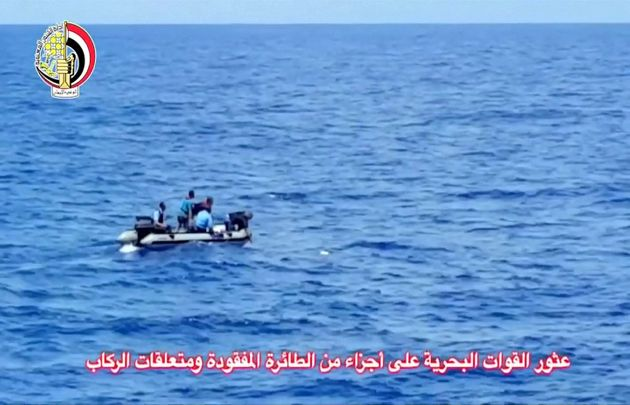 Men on a military dinghy boat remove an object from the sea as they recover debris of the crashed EgyptAir...
