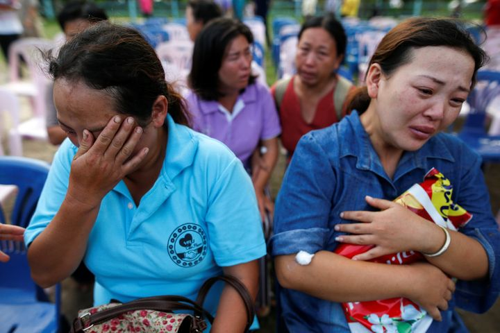Women who lost their daughters to the fire mourn near the Pitakiatwittaya School, where the fire took place.
