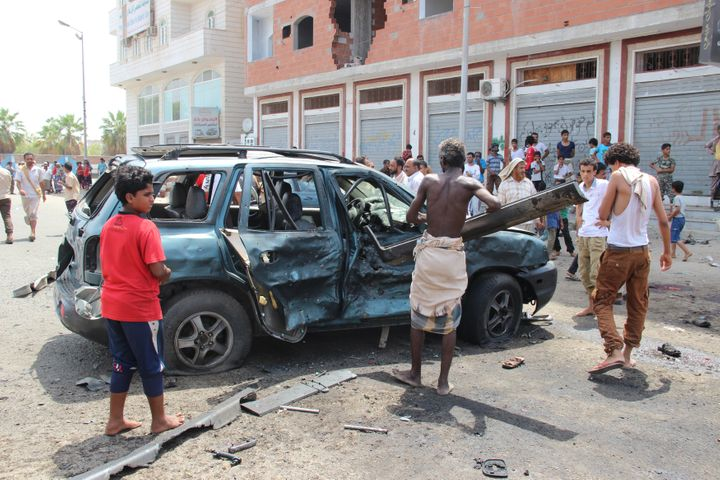 People inspect the site of the suicide bombing in Aden.