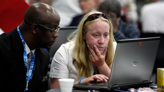 Tressa Miller, right, helps military veteran Roger Porter, of Detroit, with resume career counseling in Detroit, Tuesday, June 26, 2012. Thousands of veterans are in Detroit this week for job fair, open house, small business conference. (AP Photo/Paul Sancya)