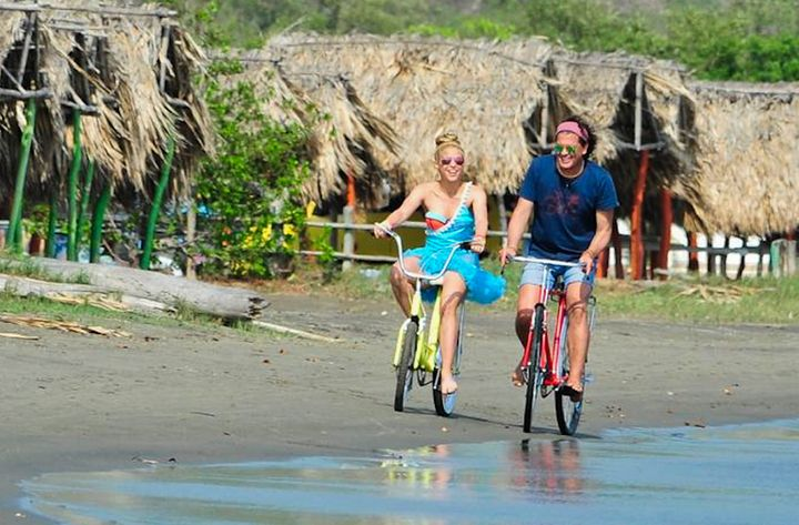 "Colombian singers Shakira and Carlos Vives ride bikes during the recording of the video for the song ""La Bicicleta."""