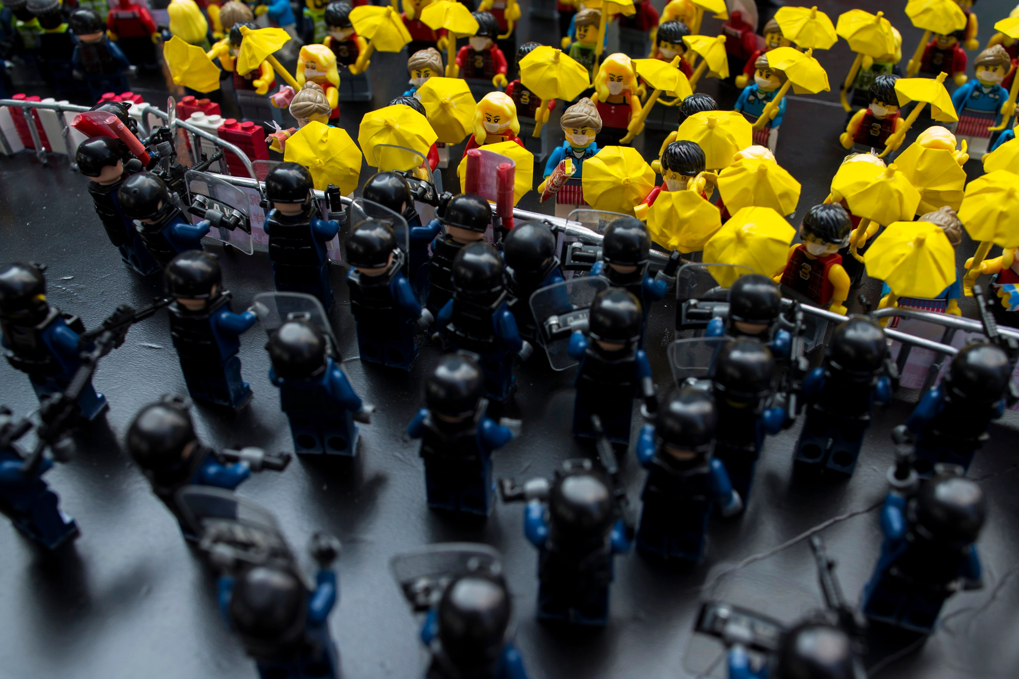 Toy Lego characters depicting a scene of protesters confronting riot police are seen on a table outside the government headqu