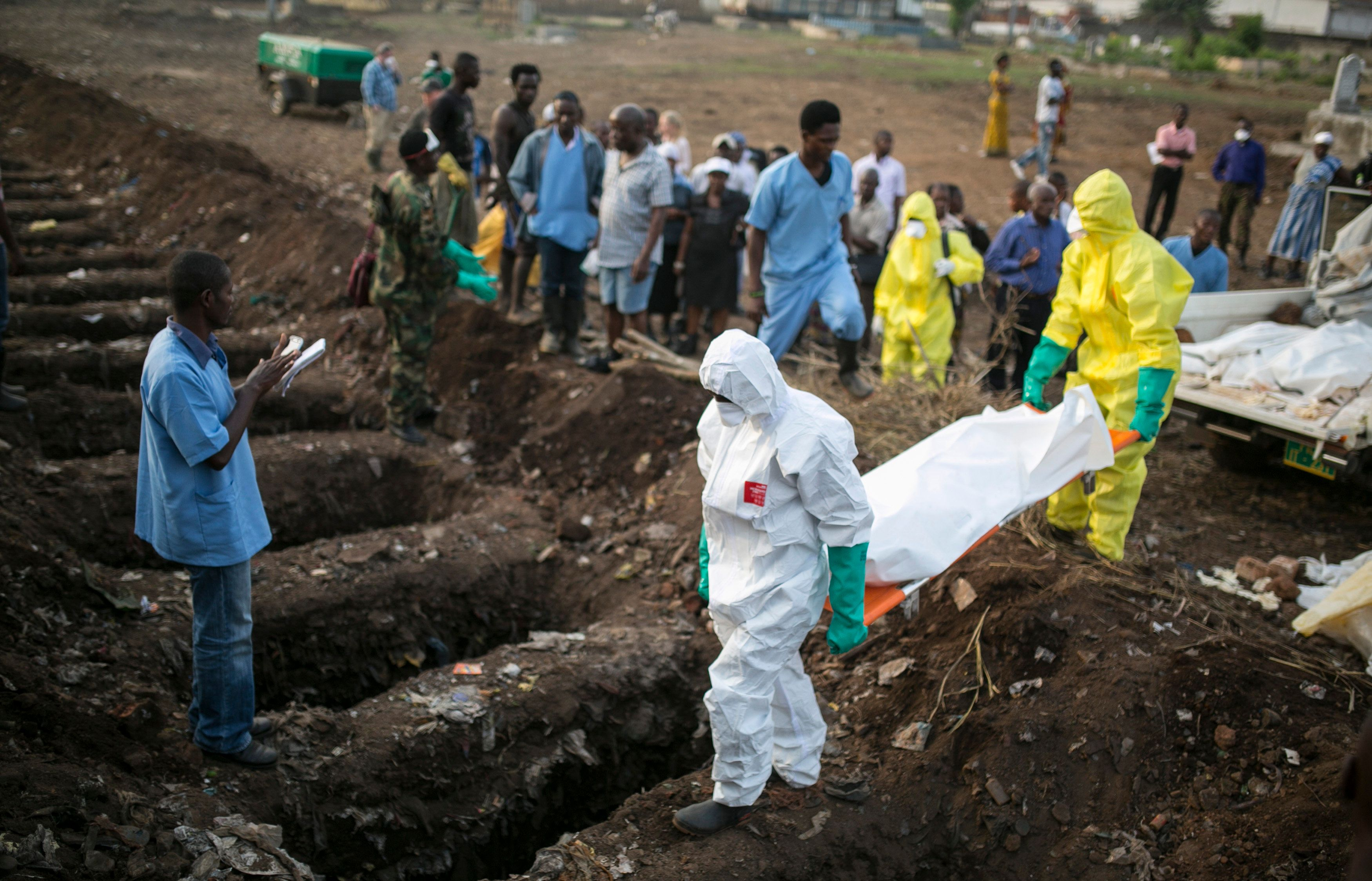 Health workers carry the body of an Ebola victim for burial at a cemetery in Freetown, December 17, 2014.  The death toll in the Ebola epidemic has risen to 6,915 out of 18,603 cases as of Dec. 14, the World Health Organization (WHO) said on Wednesday. There are signs that the increase in incidence in Sierra Leone has slowed, although 327 new cases were confirmed there in the past week, including 125 in the capital Freetown, the WHO said in its latest update. REUTERS/Baz Ratner (SIERRA LEONE - Tags: DISASTER HEALTH)