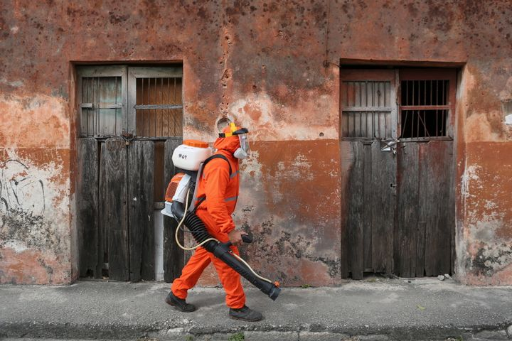 A health worker walks towards a house to fumigate it as part of preventive measures against the Zika virus in Mexico.