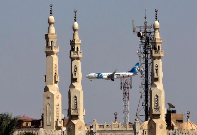 An EgyptAir plane flies past minarets of a mosque as it approaches Cairo International