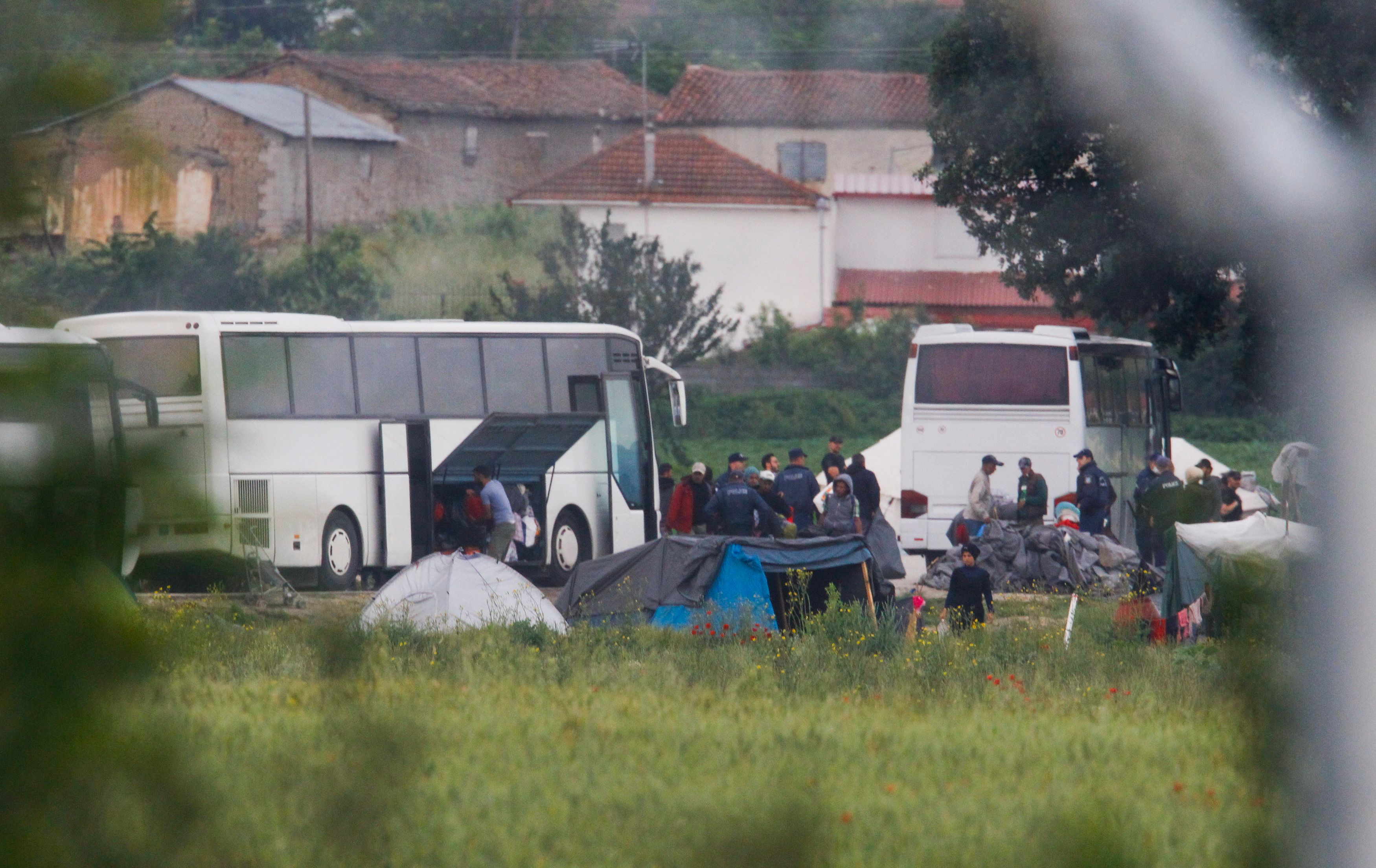 Greek policemen cleara makeshift camp for migrants and refugees at the Greek-Macedonian