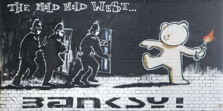 "The ""Kiss of Death"" is located just yards away from Banksy's iconic ""The Mild Mild West"" in the Stokes Croft neighborhood of"