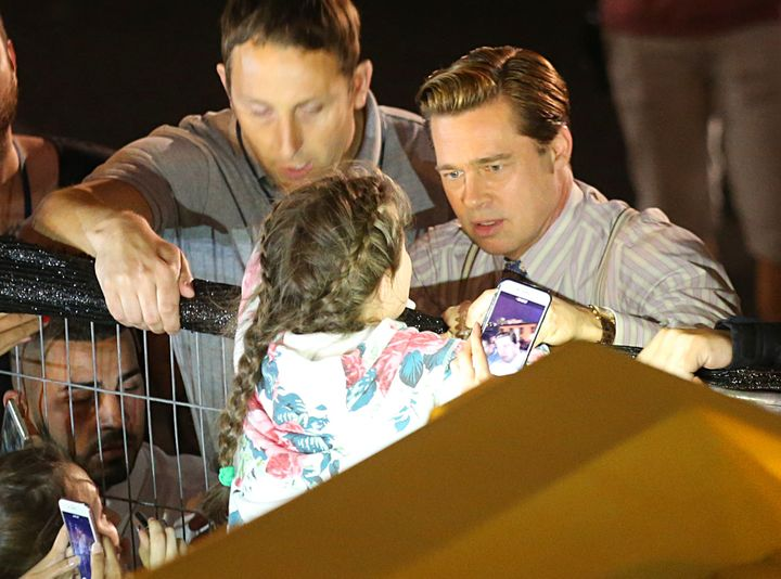Brad Pitt reaching out to help a young fan who was getting crushed by the crowd of people waiting to see him.
