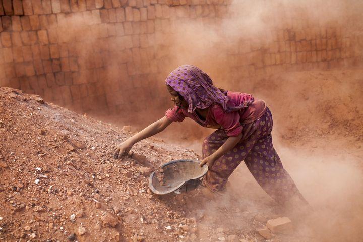 DHAKA, BANGLADESH - FEBRUARY 09 : Child labors collect coal from dust near brick making field in Dhaka, Bangladesh on Februar