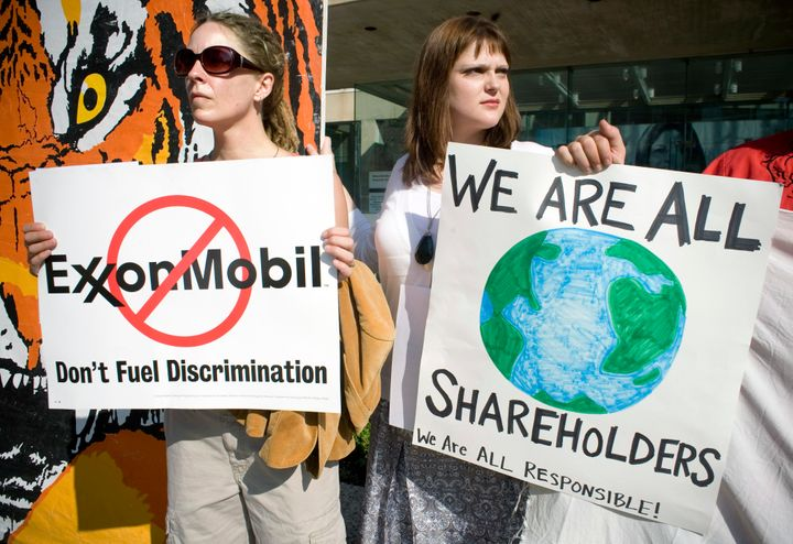 Michele Vaughan (L) and Ashlee Whitaker, both of Dallas, protest outside the ExxonMobil annual shareholders' meeting at the M
