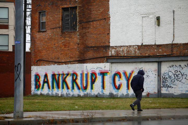 A man walk past graffiti in Detroit on Dec. 3, 2013.