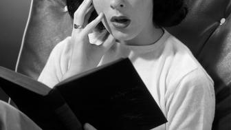 UNITED STATES - CIRCA 1950s:  Woman reading a book with a look of surprise.