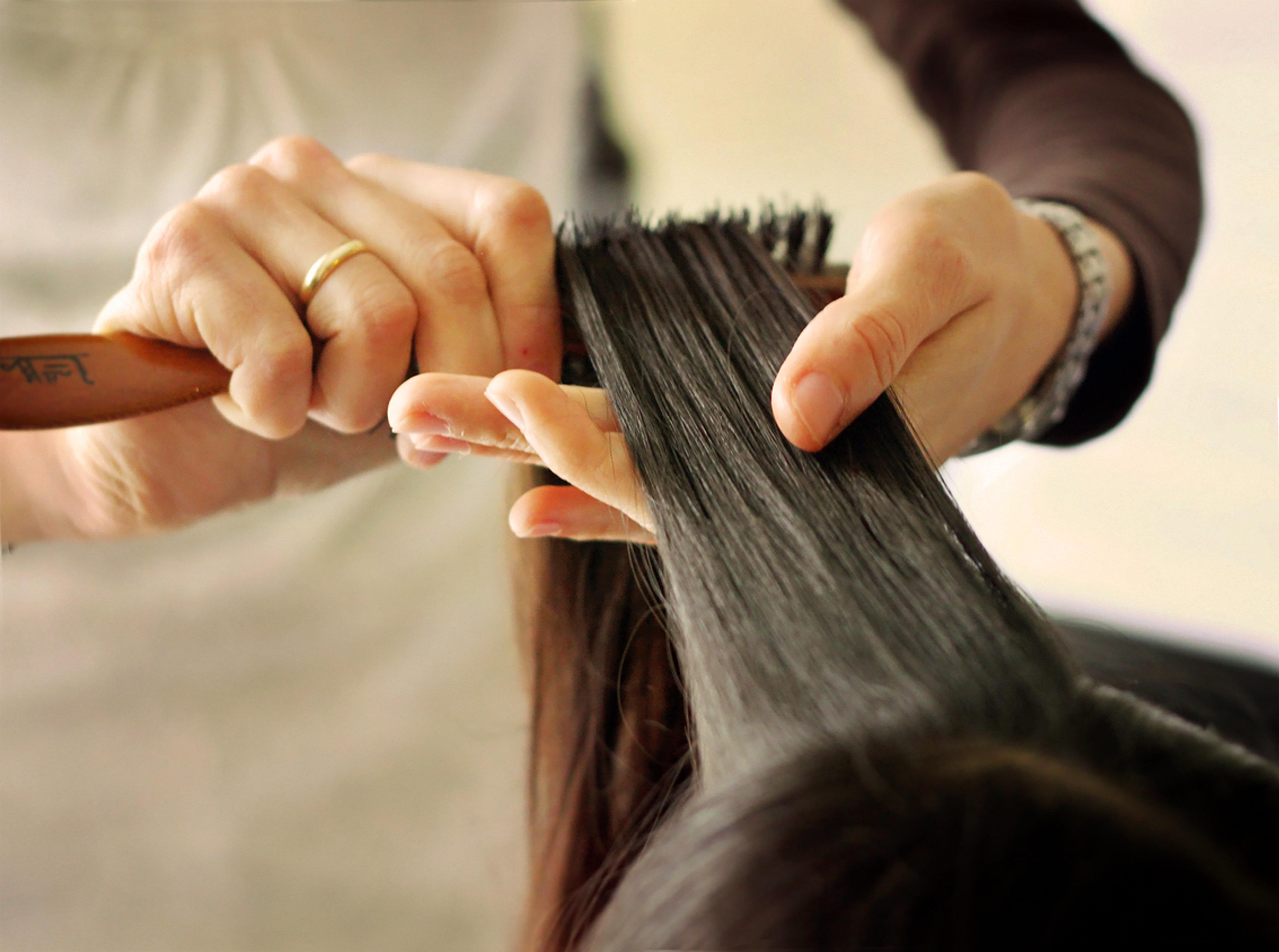 Primer plano de unas manos gentiles cepillando un mechón de cabello moreno/castaño oscuro, liso, sedoso y largo, de aspecto fuerte y sano.