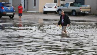 A man walks through the water on Kostoryz Road on Monday, May 16, 2016 in Corpus Christi, Texas. Thunderstorms in South Texas that dumped up to a foot of rain have led to flood-related rescues in Corpus Christi and sewage spilled into a creek.(Rachel Denny Clow/Corpus Christi Caller-Times via AP)