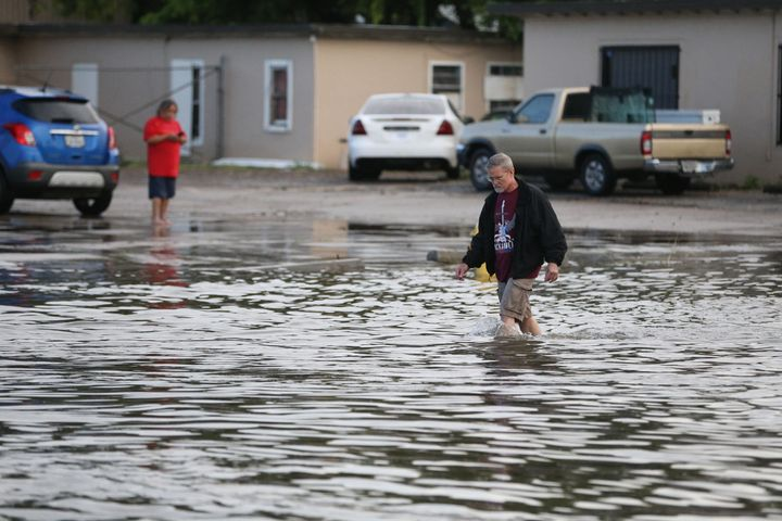 A man walks through the water on Kostoryz Road on Monday, May 16, 2016, in Corpus Christi, Texas. Storms have contributed to