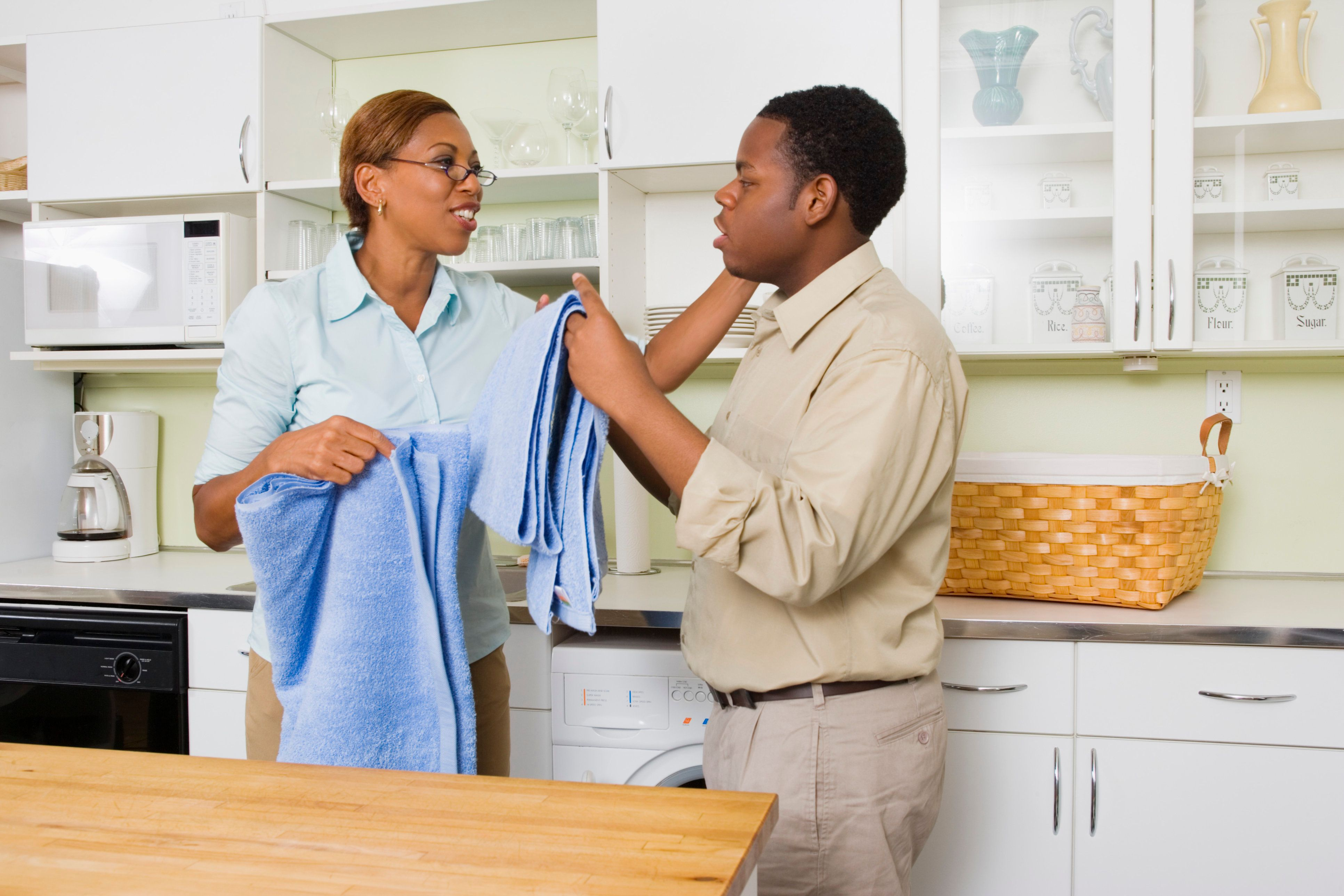 Mother and son folding towels in kitchen