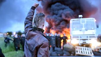 A protester holds up his fist as riot police prepare to intervene to disperse refinery worker holding a blockade of the oil depot of Douchy-Les-Mines to protest against the government's proposed labour reforms, on May 25, 2016.  Refinery workers stepped up strikes that threaten to paralyse France weeks ahead of the Euro 2016 tournament as the government moved to break their blockades, escalating a three-month tug-of-war over labour reforms. / AFP / FRANCOIS LO PRESTI        (Photo credit should read FRANCOIS LO PRESTI/AFP/Getty Images)