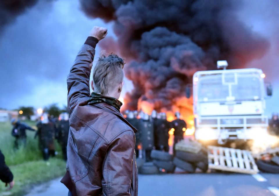 A protester raises his fist as riot police prepare to disperse refinery workers who are blockading the...