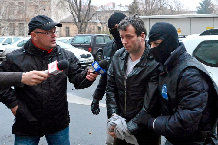 Marcel Lazar Lehel, 40, is escorted by masked policemen in Bucharest, after being arrested in Arad, 550 km (337 miles) west o
