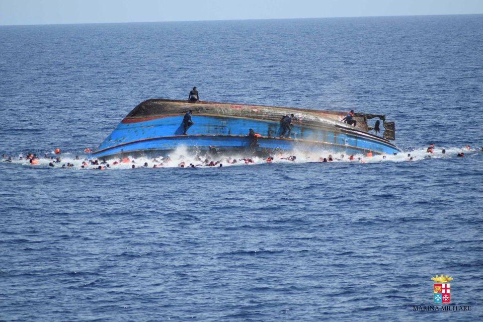 Some migrants later climbed onto the hull of the overturned vessel, while others swam for lifeboats or...
