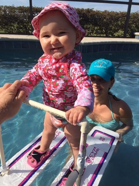 Baby Zyla, whose mother says adores water, is seen trying out a pair of water skis in a backyard pool.