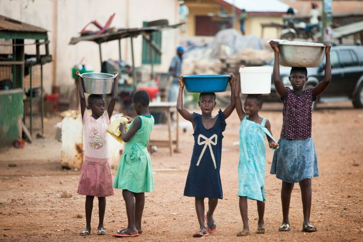 KWAMANG, GHANA - NOVEMBER 10: Young girls carry water on their heads in their cocoa-producing village, on November 10, 2015 i