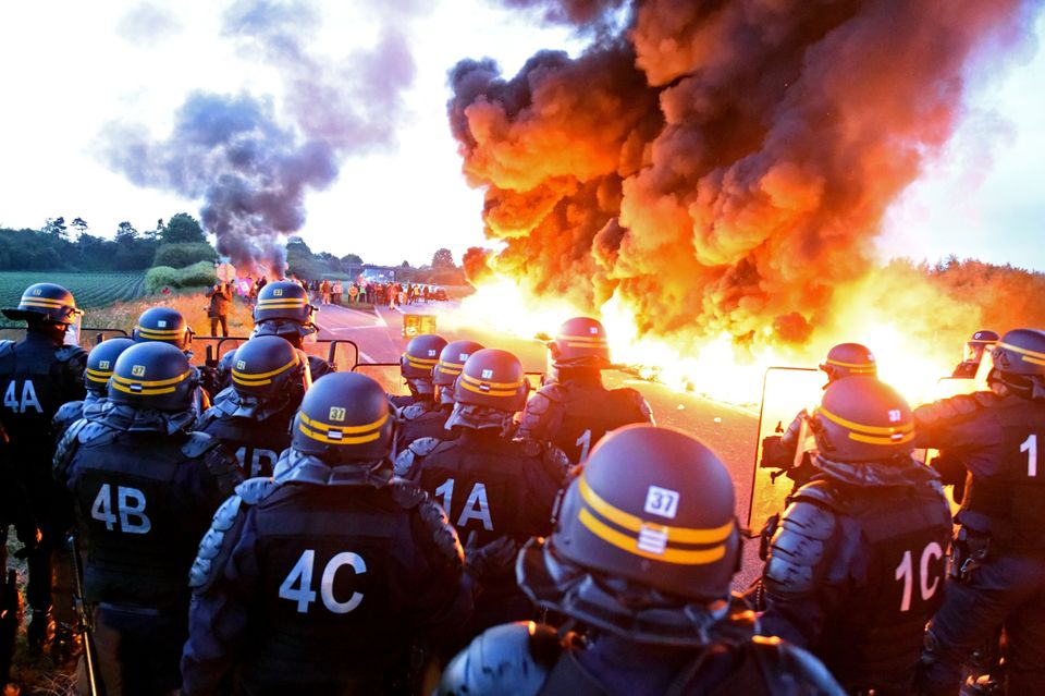 Riot police watch as a wall of flame separates them from refinery workers blockading the oil depot...