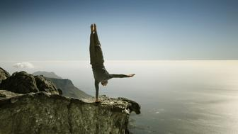 Man practicing yoga on rocky cliff