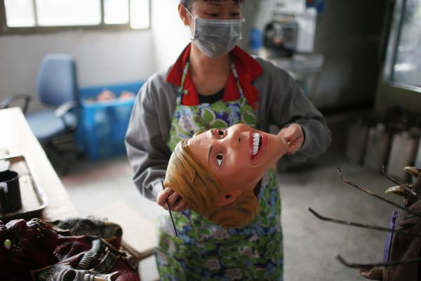 A worker inspects a mask of Hillary Clinton.