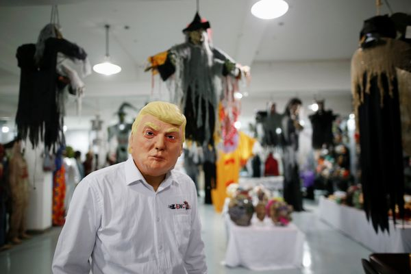 Now he poses in a Donald Trump mask.