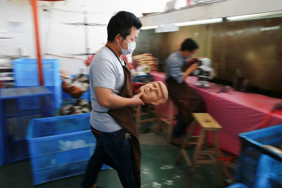 A worker carries a freshly made mask of Donald Trump at the Jinhua Partytime Latex Art and Crafts Factory in China.