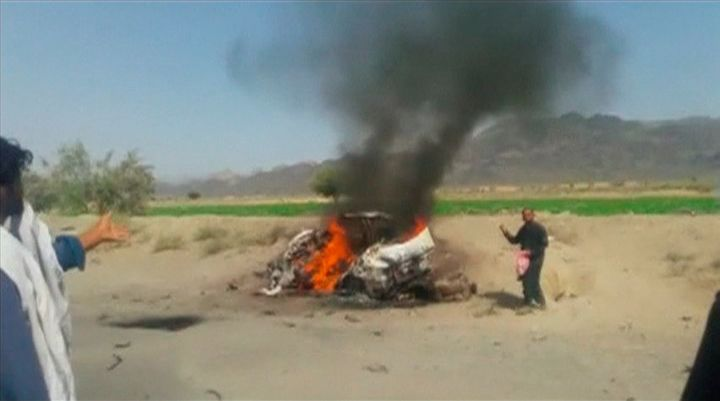 A car is seen on fire at the site of a drone strike believed to have killed Afghan Taliban leader Mullah Akhtar in southwest
