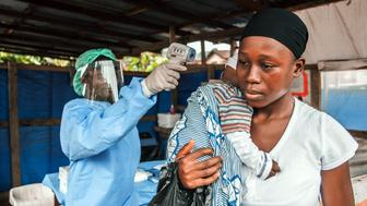 A woman visits the Macauley government hospital in Freetown, Sierra Leone, with her baby on Thursday, Jan. 21, 2016. She is having her temperature taken prior to entering, as part of Ebola prevention.