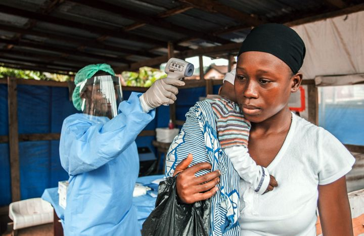 A woman visits the Macauley government hospital in Freetown, Sierra Leone, with her baby. She is having her temperature taken