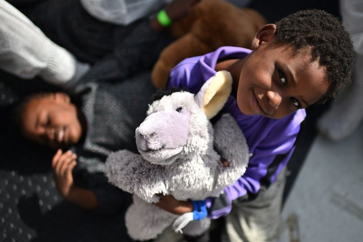 A child smiles during a distribution of meals aboard the rescue ship 'Aquarius', on May 25, 2016 a day after a rescue operati