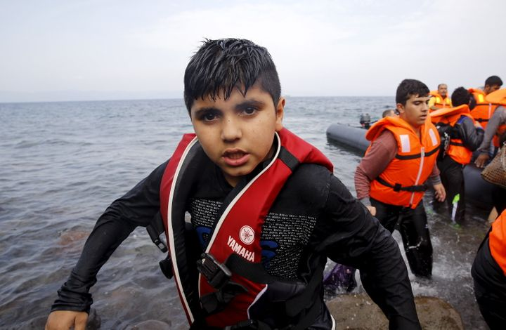 A Syrian refugee boy desembarks from a raft at a beach on the Greek island of Lesbos after crossing a part of the Aegean Sea