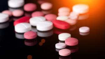 Group of different colorful tablets on black background with reflection