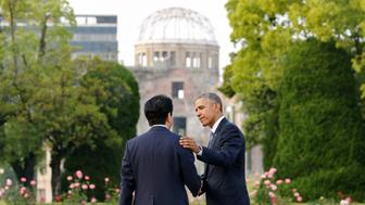 U.S. President Barack Obama (R) puts his arm around Japanese Prime Minister Shinzo Abe after they laid wreaths in front of a cenotaph as the atomic bomb dome is background at Hiroshima Peace Memorial Park in Hiroshima, Japan May 27, 2016. REUTERS/Kimimasa Mayama/Pool